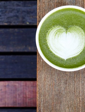 Matcha in a mug on a wooden railing,