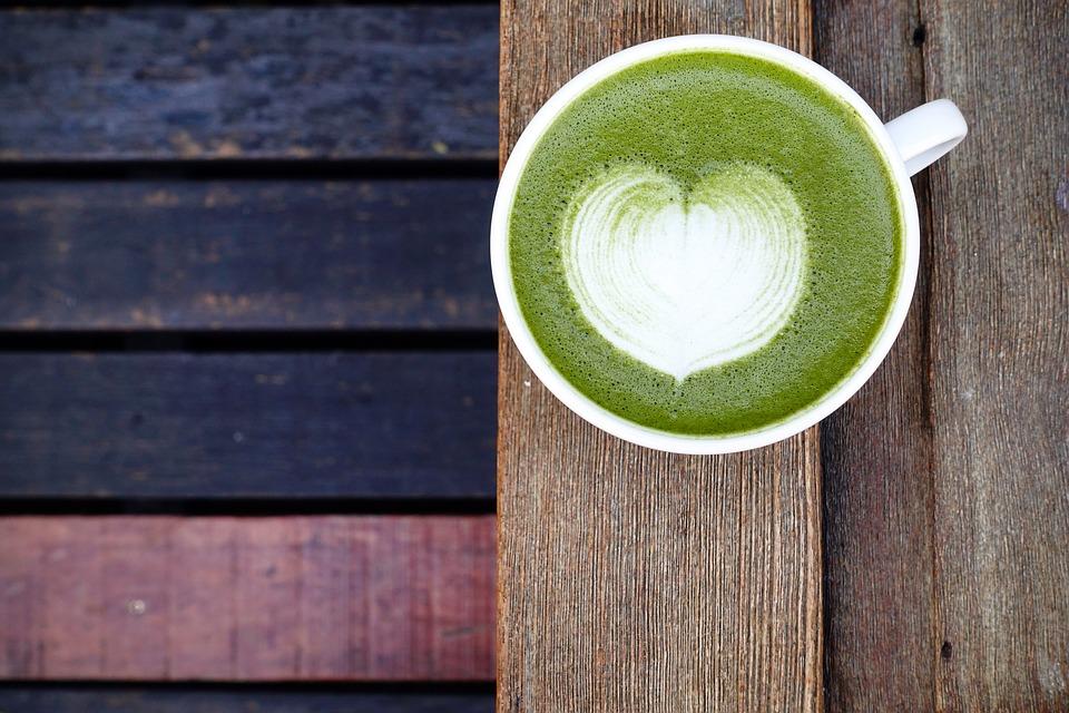 Matcha in a mug on a wooden railing,