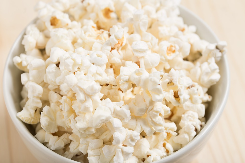 Popcorn in a bowl on a wooden surface.