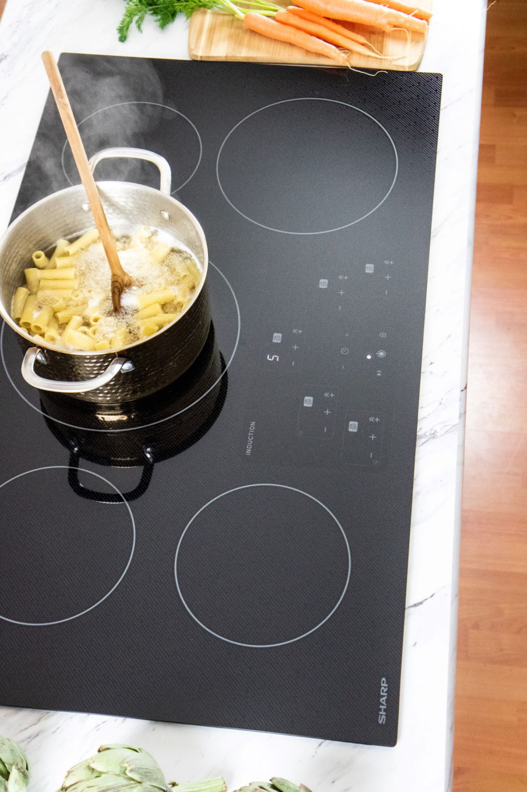 Pasta cooking in a 3pot on an induction cooktop.