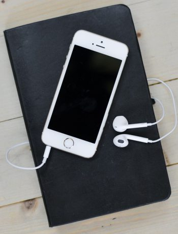 Smartphone with earphones on top of a journal on a wooden surface.