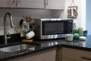 Sharp Microwave Oven- SMC1449FS next to Alexa device