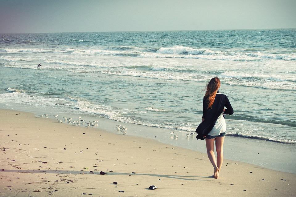 Woman walking on the beach alongside the ocean.