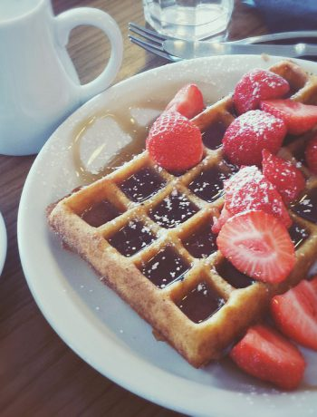Plate of waffles and fruit with a cup of coffee