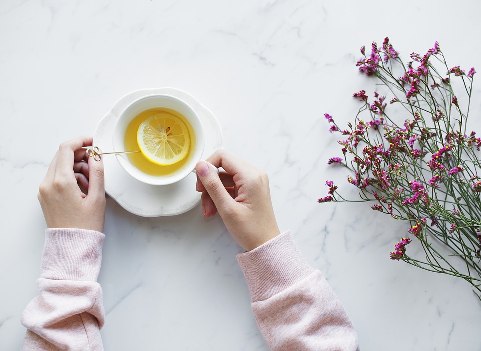 Teacup and lemon on a white countertop next to flowers.