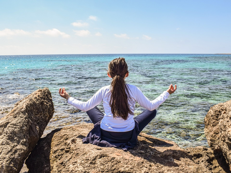 Woman practicing meditation on a rock facing a body of water.
