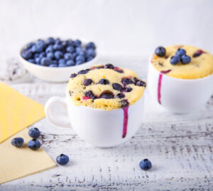 Blueberry muffins in a white mug and a bowl of blueberries on white wooden table