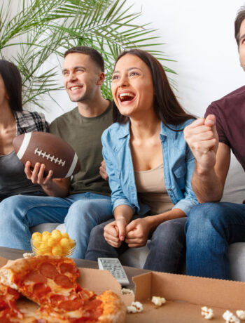 group of friends watching a sports game, holding a football and eating pizza and snacks