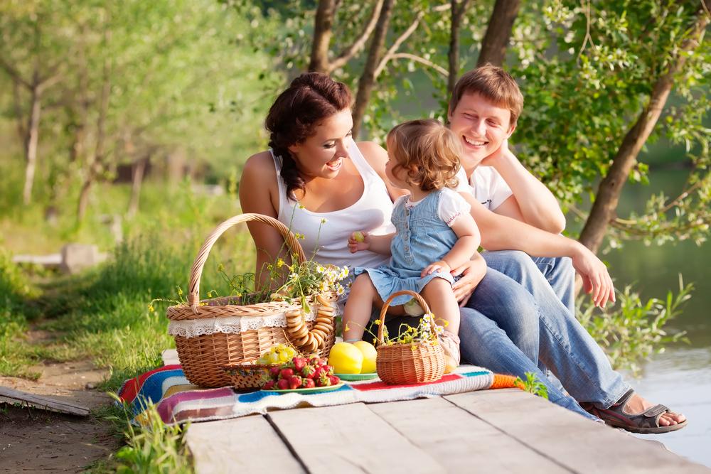 Family of three enjoying a picnic outdoors