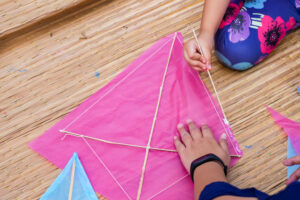 Pink paper kite on the floor with hands working on it