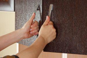 Opening cabinet door with two hands.