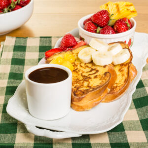 French toast meal with coffee, strawberries, and bananas on a checkered pattern