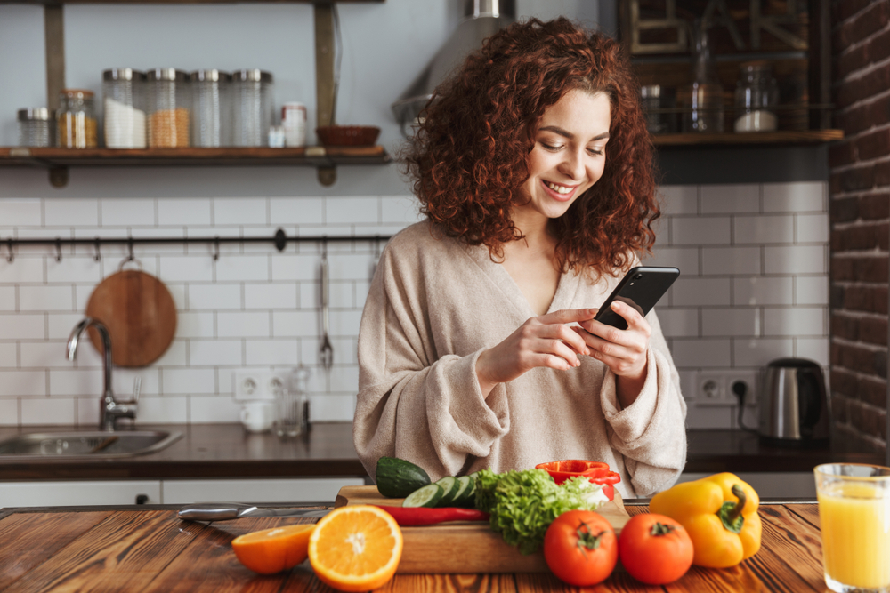 Woman on her phone in the kitchen