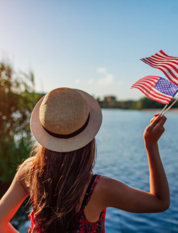 Woman standing near body of water with flag