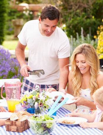 Family Enjoying Outdoor Barbeque In Garden