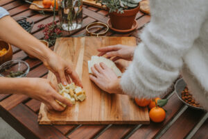 Wooden charcuterie board with hands arranging food