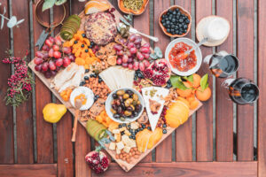 Charcuterie board with fruits and jams on a wooden board and table
