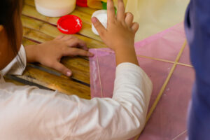 Child building a pink kite on a wooden table