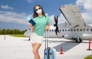 Female summer traveler at the airport with a mask.