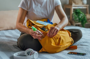Close,Up,Of,Young,Woman,Packing,Her,Backpack,With,Hand