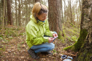 Woman geocaching in the woods holding a geocache she found.