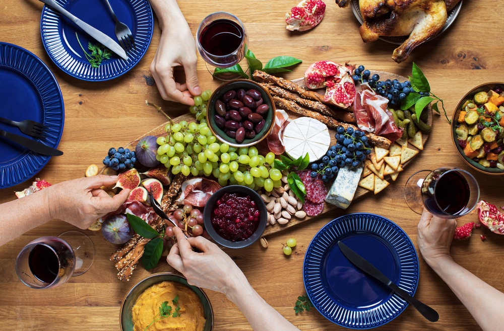 People eating a charcuterie board with fruit, meat, cheese, and crackers with a wooden background