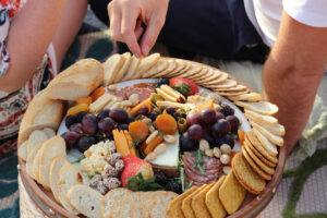 Hands picking at a charcuterie board with cheese, crackers, meats, and other food on the tray