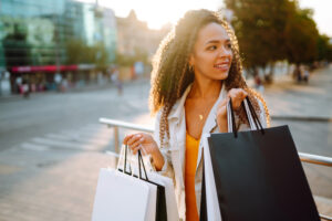 Woman shopping for Labor Day Promotions with bags in hand.