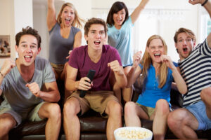 crowd watching a sporting event cheering while eating popcorn