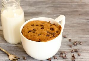 Chocolate chip cookie in a white mug, glass of milk, and scattered chocolate chips on a rustic background