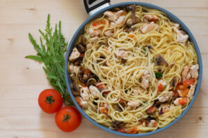 pasta in a pan with tomatoes and mushrooms on a wooden surface