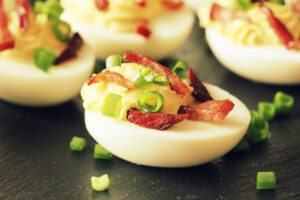 Deviled eggs with bacon on a black background