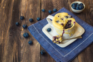 Blueberry muffin in a white mug and blueberries on a blue napkin on a wooden surface