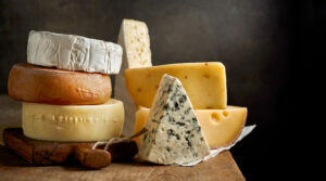Different types of cheeses piled on one another on wood