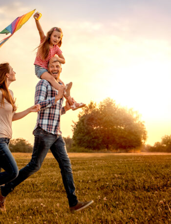 Family flying a kite in an open field
