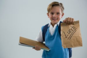 Kid holding a brown paper bag