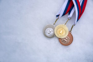 Gold, silver, and bronze metal on a snowy surface.