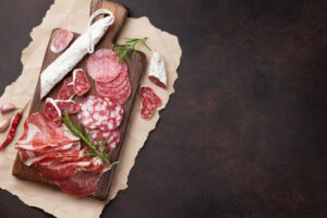 An array of different meat on a board with a dark background